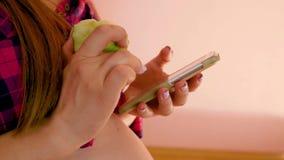 Una vista laterale di una donna incinta che mangia una mela, esaminando il telefono cellulare a disposizione, controllando inform video d archivio