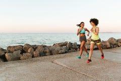 Una vista laterale di due donne di forma fisica che corrono all'aperto Immagini Stock Libere da Diritti
