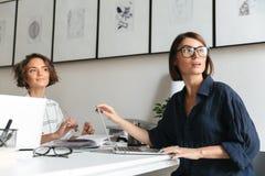 Una vista laterale di due donne graziose che si siedono dalla tavola Immagini Stock