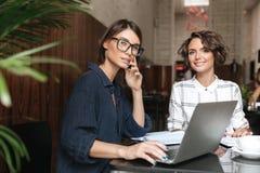 Una vista laterale di due responsabili femminili che si siedono dalla tavola Immagine Stock