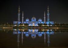 Una vista nocturna de Sheikh Zayed Grand Mosque de una reflexión del agua imagenes de archivo
