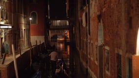 Una vista nocturna del canal de Venecia con una góndola almacen de metraje de vídeo