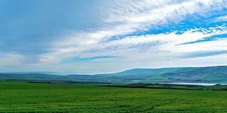 Una vista panorámica de un campo con el cielo magnífico Fotografía de archivo libre de regalías