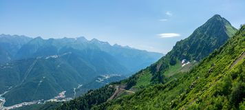 Una vista panorámica del valle con las construcciones de viviendas, rodeada por las montañas con los teleféricos imágenes de archivo libres de regalías