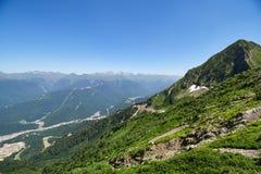 Una vista panor?mica del valle con las construcciones de viviendas, rodeada por las monta?as con los telef?ricos imagen de archivo