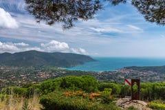 Una vista panoramica di una delle spiagge dell'isola di Elba e di una cittadina vicino alla spiaggia nella laguna verde smeraldo  immagini stock