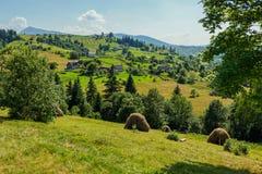 Una vista pittoresca di un villaggio rurale situato in mezzo alle catene montuose verdi Immagine Stock