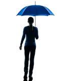 Vista posterior de la mujer que camina sosteniendo la silueta del paraguas Fotografía de archivo