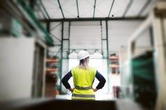 Una vista posterior de una situación industrial del ingeniero de la mujer en una fábrica, brazos en caderas foto de archivo