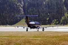 Una vista posterior de un jet privado en las montañas Suiza en tiempo de verano fotografía de archivo libre de regalías