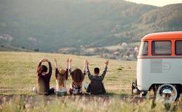 Una vista posterior del grupo de amigos jovenes que se sientan en hierba en un roadtrip a través de campo foto de archivo