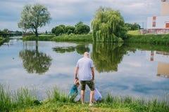 Una vista posterior del padre con el hijo al aire libre por el lago en verano fotos de archivo libres de regalías