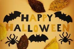 Una vista sul segno felice di Halloween con i pipistrelli ed i ragni neri Inoltre possiamo vedere le foglie di autunno Trucco o t immagine stock