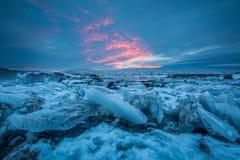 Una vista sulle banchise galleggianti di cottura, sotto un cielo colorato di tramonto vicino alle cascate Immagine Stock