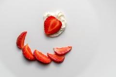 Una vista superior de fresas y de la crema cortadas en una placa blanca Los pedazos de bayas se presentan agradable en una placa imagen de archivo libre de regalías