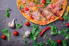 Una vista superior de una pizza colorida y sustanciosa con los tomates rojos, el queso y las salsas picantes en un fondo gris osc fotografía de archivo libre de regalías