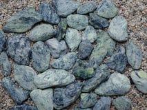 Una vista superiore delle pietre blu del mare su un fondo variopinto della sabbia Decorazione per la casa Struttura, concetto del Fotografia Stock