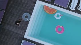 Una vista superiore dello stagno con i cerchi gonfiabili multicolori e i chairses del sole che fanno una pausa lo stagno Fucilazi stock footage