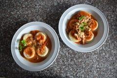 Una vista superiore di due piatti dei sorrentinos - pasta farcita - con salsa, parmigiano e decorato con le foglie di alcuni pars immagini stock