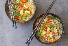 Una vista superiore di due piatti orientali con un piatto del vegano delle tagliatelle, del tofu e degli ortaggi freschi di vetro fotografia stock
