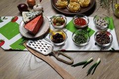 Una vista superiore di due tipi di formaggio e di olive sui precedenti di pasta, della cipolla, dell'aglio e del pepe su un tovag fotografia stock