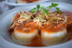 Una vista superiore di un piatto dei sorrentinos - pasta farcita - con salsa, parmigiano e decorato con le foglie di alcuni parsl fotografia stock