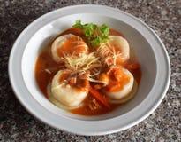 Una vista superiore di un piatto dei sorrentinos - pasta farcita - con salsa, parmigiano e decorato con le foglie di alcuni parsl fotografie stock