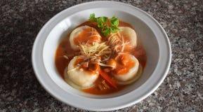 Una vista superiore di un piatto dei sorrentinos - pasta farcita - con salsa, parmigiano e decorato con le foglie di alcuni parsl immagine stock libera da diritti