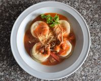 Una vista superiore di un piatto dei sorrentinos - pasta farcita - con salsa, parmigiano e decorato con le foglie di alcuni parsl fotografia stock libera da diritti