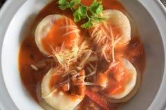 Una vista superiore di un piatto dei sorrentinos - pasta farcita - con salsa, parmigiano e decorato con le foglie di alcuni parsl fotografie stock libere da diritti