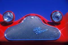 Una visualizzazione dettagliata di una griglia e di un insetto altamente lucidati del cromo ha osservato i fari su un'automobile  Fotografia Stock Libera da Diritti