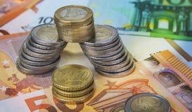 Una y dos monedas euro apiladas con los billetes de banco de papel Foto de archivo libre de regalías