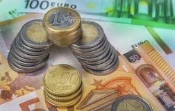 Una y dos monedas euro apiladas con los billetes de banco de papel Fotografía de archivo libre de regalías