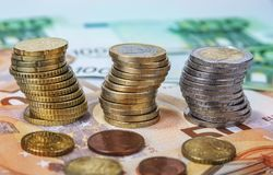 Una y dos monedas euro apiladas con los billetes de banco de papel Fotos de archivo
