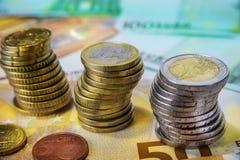 Una y dos monedas euro apiladas con los billetes de banco de papel Imágenes de archivo libres de regalías