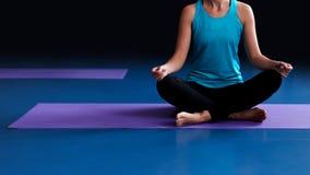 Una yoga practicante de la mujer en una estera Imagen de archivo libre de regalías