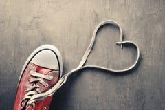 Una zapatilla de deporte en fondo concreto con un corazón Imagenes de archivo