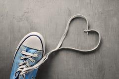 Una zapatilla de deporte en fondo concreto con un corazón Imagen de archivo