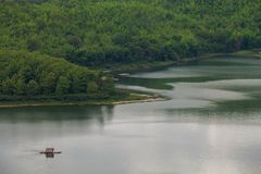 Una zattera sta galleggiando sull'acqua in diga dietro verde del fondo della montagna fotografia stock libera da diritti