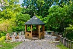 Una zona de recreo pintoresca con una pérgola de madera con un tejado verde y los bancos en los lados Fotos de archivo libres de regalías