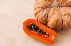 Una zucca gialla e una papaia arancio della Tailandia sulla parete di legno Fotografia Stock