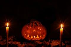 Una zucca terribile di Halloween con una mano che si trova su  basamenti Immagine Stock