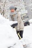 Unabhängige Frau, die Schnee im Winter schaufelt Stockbilder