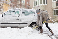 Unabhängige Frau, die Schnee im Winter schaufelt Stockfotografie