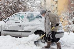 Unabhängige Frau, die Schnee im Winter schaufelt Lizenzfreies Stockbild