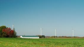 Unabhängige Stromversorgung in der Landwirtschaft Windkraftanlagen nahe einem typischen Bauernhof und einem Aufzug stock footage