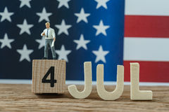 Unabhängigkeitstag USA mit dem Miniaturgeschäftsmann, der auf Holz steht Lizenzfreies Stockbild