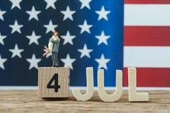 Unabhängigkeitstag USA mit junger Paarstellung der Miniaturleute Stockfotografie
