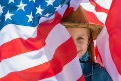 Unabh?ngigkeit Day Sch?nes gl?ckliches M?dchen mit gr?nen Augen auf dem Hintergrund der amerikanischen Flagge an einem hellen son lizenzfreies stockfoto