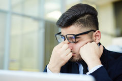 Unable to concentrate. Tired businessman trying to concentrate during work after sleepless night Stock Images
